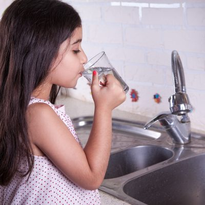 One beautiful middle eastern little girl with pink dress and long dark brown hair and eyes on white kitchen, helping parents to wash dishes and drinking water and smiling.